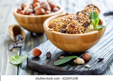 Cereal bars with hazelnuts,peanuts and chocolate in bowl on wooden table, selective focus.