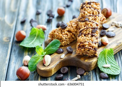 Cereal bars with nuts and chocolate on old wooden table, selective focus.