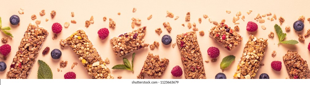 Cereal bars on a bright pastel background, top view.