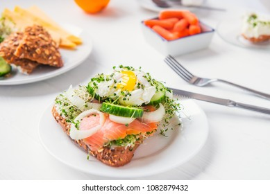 Cereal bun with egg benedict, smoked salmon, sprout micro greens, onion and cucumber slices, cream cheese on the served white wooden table. Healthy breakfast concept. Selective focus