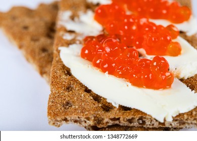 Cereal crispbread crackers with butter and red caviar. Extreme closeup