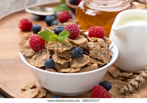 cereal flakes with fresh berries, honey and milk for breakfast, close-up