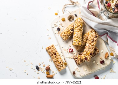 Cereal granola bar with nuts, fruit and berries on a white stone table. Healthy sweet dessert snack. Top view copy space.