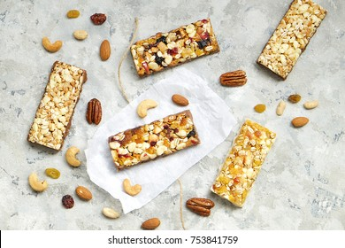 Cereal granola bars with nuts and fruit berries, with ingredients on a stone table. Top view healthy snack.