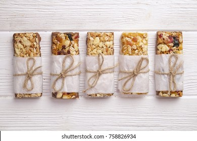 Cereal superfood energy bars with almond nuts, dry fruits, raisins chocolate on the white wood table, top view