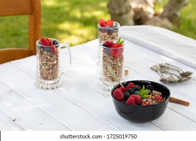 Cereals and berries in cups and bowl on white breakfast table outside in the garden