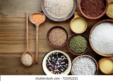 Cereals and legumes in bowls on wooden background. Top view