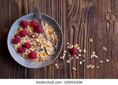 Cereals, muesli, granola with fresh raspberries on dark wooden table for healthy breakfast