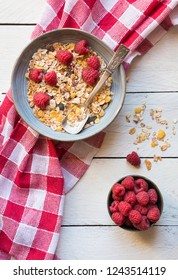 Cereals, muesli, granola with fresh raspberries on white wooden table for healthy breakfast