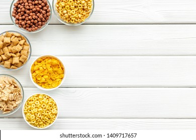 cereals, oatflakes and cornflakes for healthy breakfast on white wooden background top view mock up