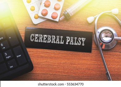 CEREBRAL PALSY words written on label tag with medicine,syringe,keyboard and stethoscope with wood background,Medical Concept