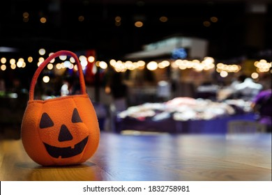 cerebration halloween carnival with pumpkin bag for candy trick or treat party at night show on wood table