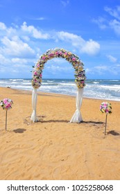 Ceremonial wedding arch on the beach. Wedding decoration from flowers.