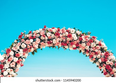 Ceremonial wedding arch on the beach decorated with natural flowers