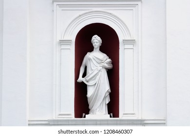 Ceres - the goddess of agriculture. Classical sculpture of a girl with a sickle and ears in a niche wall. Sculpture of white plaster.