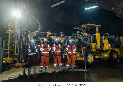 Cerro de Pasco, Peru - July 13th 2017: Miners inside the mine posing for the photo, behind them a large machine.