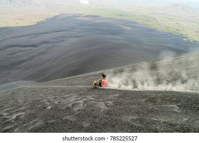 CERRO NEGRO, NICARAGUA - APRIL 26, 2016: Tourist is volcano boarding from Cerro Negro volcano, Nicaragua