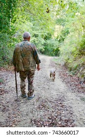 CERTALDO, ITALY – OCTOBER 12, 2017: A truffle hunter walks down a path in the forest as his dog searches for the scent of truffles in Certaldo.