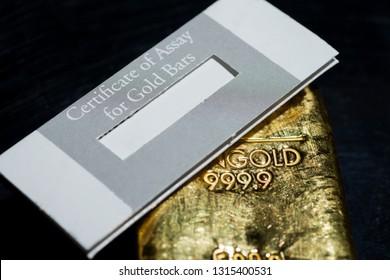 The certificate of assay for gold bars lies on a cast gold ingot. gehaltszertifikat für Goldbarren is certificate of assay for gold bars