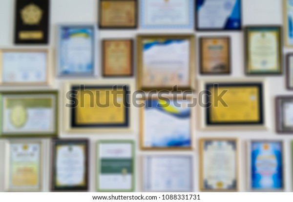 Certificates, diplomas and awards in frames on the wall. Abstract blurry background image.