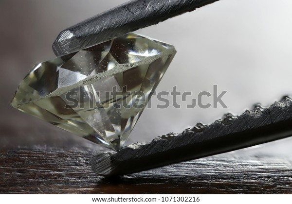 certified 0.45 ct brilliant cut diamond with laser inscription held by tweezers