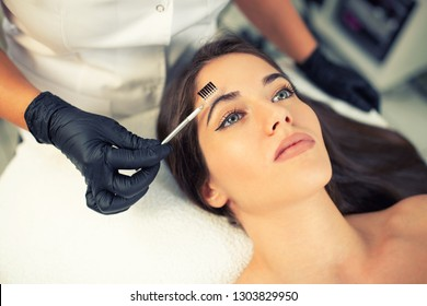 Certified beautician preparing her client eyebrows in order to apply more precise and hair-like strokes