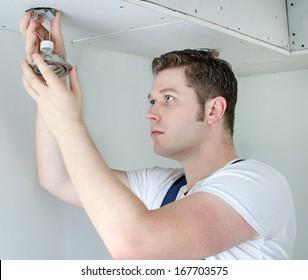 Certified electrician installing light bulb