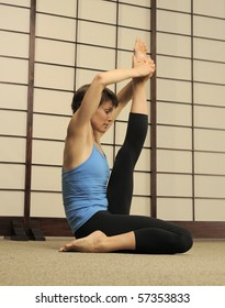 Certified Pilates instructor demonstrates difficult stretching workout in exercise studio.