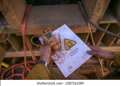 Certifies miner hands holding gas test detector confined space permit book and inspecting safety environment surrounding before conduct gas testing prior to work in confined space mine site Perth, WA