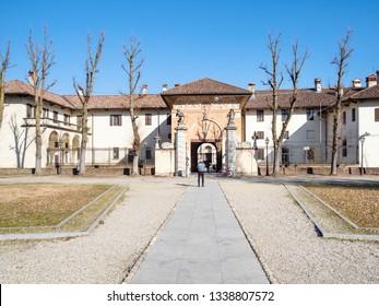 CERTOSA DI PAVIA, ITALY - FEBRUARY 22, 2019: tourist near entrance to Certosa di Pavia Gra-Car (Carthusian Monastery, Monastero di Santa Maria delle Grazie, Santuario Gratiarum Carthusia) in spring