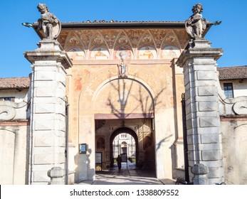 CERTOSA DI PAVIA, ITALY - FEBRUARY 22, 2019: tourist passaes gate to Certosa di Pavia Gra-Car (Carthusian Monastery, Monastero di Santa Maria delle Grazie, Santuario Gratiarum Carthusia) in spring