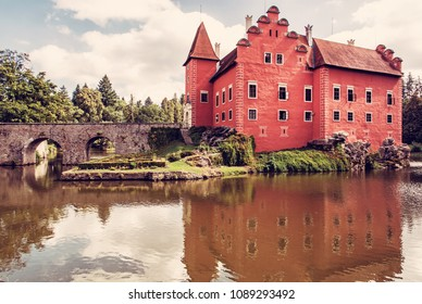 Cervena Lhota is a beautiful chateau in Czech republic. It stands at the middle of a lake on a rocky island. Travel destination. Mirrored architecture. Red photo filter.