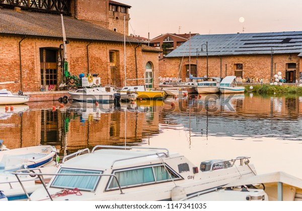 CERVIA (RA), ITALY - JULY 26, 2018: The waters are lapping the hulls of the moated boats