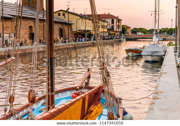 CERVIA (RA), ITALY - JULY 26, 2018: tourists are enjoying dinner at the typical restaurants while the waters are lapping the hulls of the moated boats