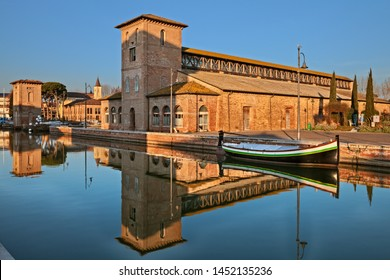 Cervia, Ravenna, Emilia Romagna, Italy: the port canal with the ancient salt warehouse and an historic fishing boat of the Adriatic sea