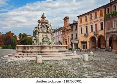 Cesena, Emilia-Romagna, Italy: the ancient fountain Fontana del Masini (16th century) and the old buildings in the square Piazza del Popolo