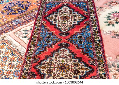 CESENA, ITALY - NOVEMBER 18, 2018: lights are enlightening ancient Eastern rugs for sale in Antiques Fair