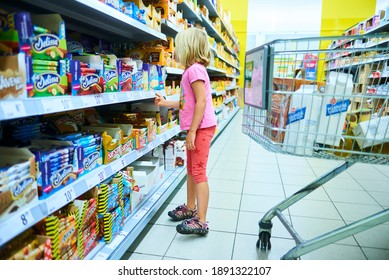 Ceska lipa, Czech Republic - September 19 2015: Little Child Blond Girl Shopping in the supermarket, pushing trolley, looking for goods in the store