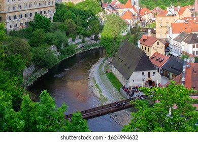 Cesky Krumlov, Czech Republic; 5/18/2019: Aerial view of the traditional colorful houses of Cesky Krumlov and Vltava river with Lavka pod Zamkem (the bridge underneath the Castle)