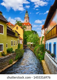 Cesky Krumlov (Czech Krumlov), Czech Republic. View to Castle Tower in the ancient bohemian village with antique houses. Summer landscape with blue sky and clouds.