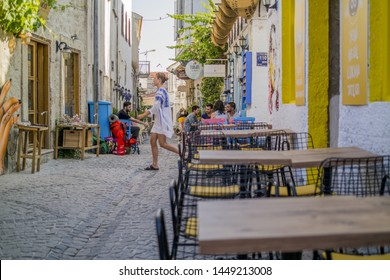 Cesme, Izmir / TURKEY - July 09 2019 : Girl passing through in the Street of alacati and tables of restaurants are empty
