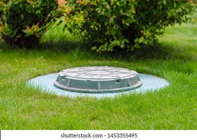 cesspool on the backyard green lawn
