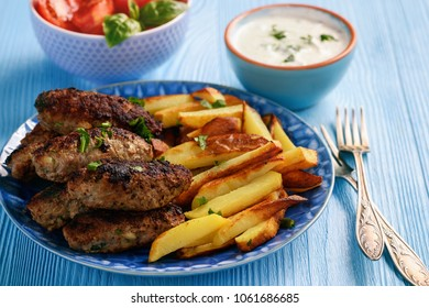 Cevapcici, balkanian grilled meat sausages with fries and yogurt dip.