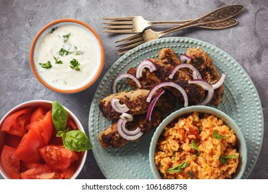 Cevapcici, balkanian grilled meat sausages with savory rice and yogurt dip.