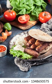 Cevapcici or cevapi served with lepinja bread and onion. Popular dish all over the Balkans