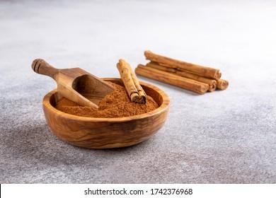 Ceylon cinnamon sticks with cinnamon powder in wooden bowl on concrete background. Copy space.