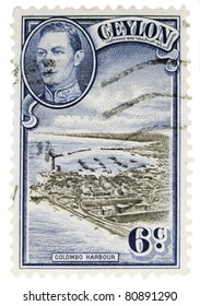 """CEYLON - CIRCA 1950: A vintage Ceylonese postage stamp image of a harbor and an inset of King George, with inscription of """"Colombo Harbour"""" value of 6 cents, series circa 1950"""