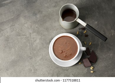 Cezve and cup of hot chocolate on grey table