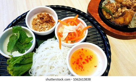cha ca la vong - pan fried fish with onion, rice vermicelli, mint leaves, fried shallots, peanuts, pickles, sweet and sour chilli sauce, serve over a basket and hot metal pan