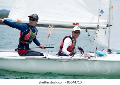 CHA-AM, THAILAND - AUGUST 26: Navee Thammasunthorn of Thailand (R) & his crew compete during Day 4 of the 2011 Hua Hin Regatta on August 26, 2011 at Dusit Thani Resort & Spa Hua Hin in Cha-Am, Thailand